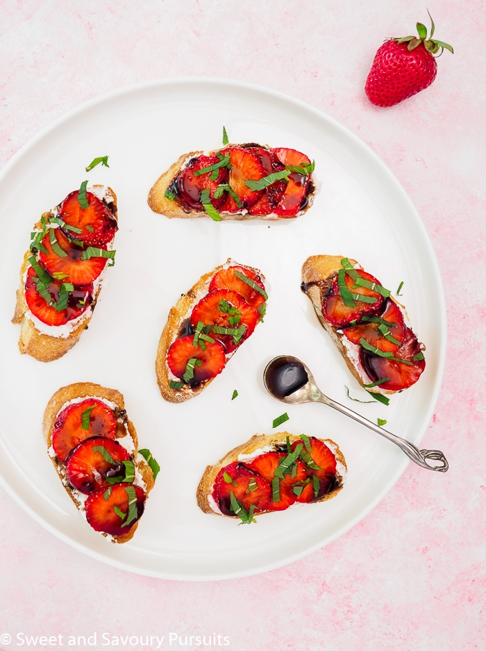 Strawberry Goat Cheese Crostini with balsamic glaze on white dish.