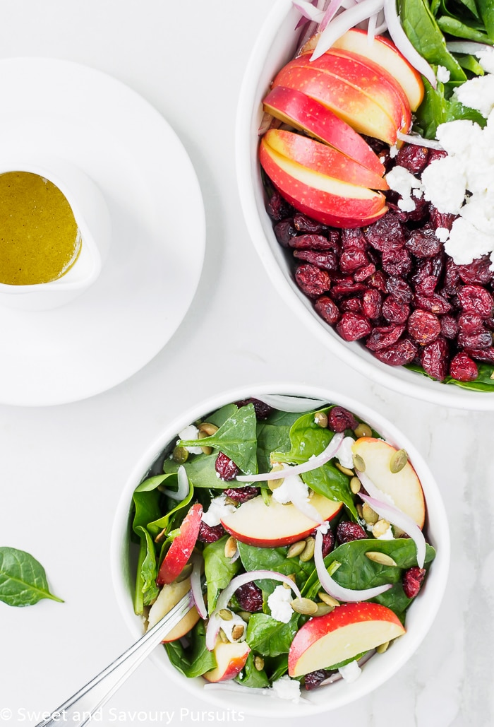Bowl of Spinach Apple Cranberry Salad with Pumpkin Seeds served with Apple Cider Vinaigrette on the side.