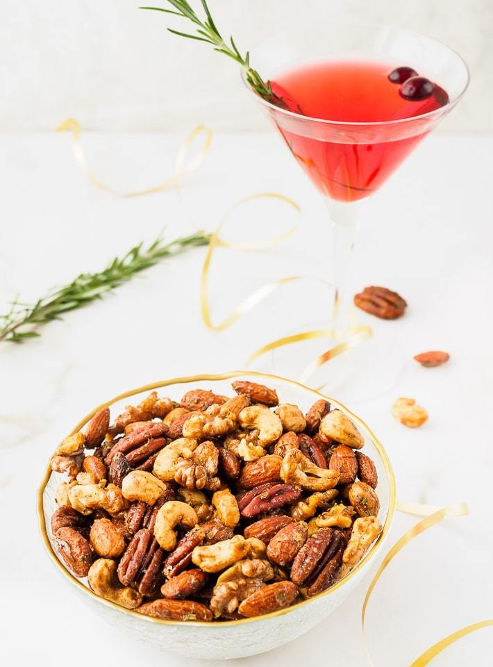 Bowl of seasoned nuts served with a cocktail.