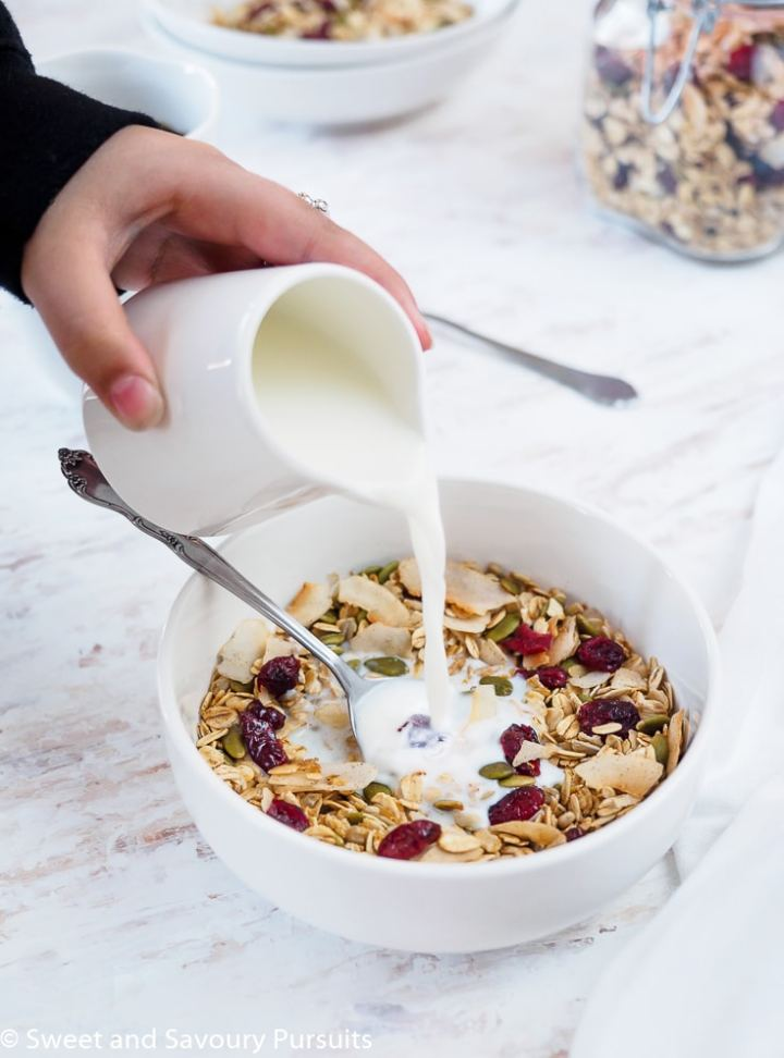 Bowl of homemade muesli made with oats, coconut flakes, dried cranberries, pumpkin and sunflower seeds being topped with milk.