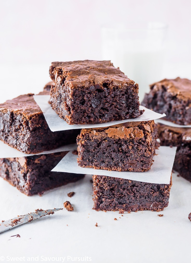 Sliced Gluten-Free Almond Flour Brownies on board with a glass of milk in the background.