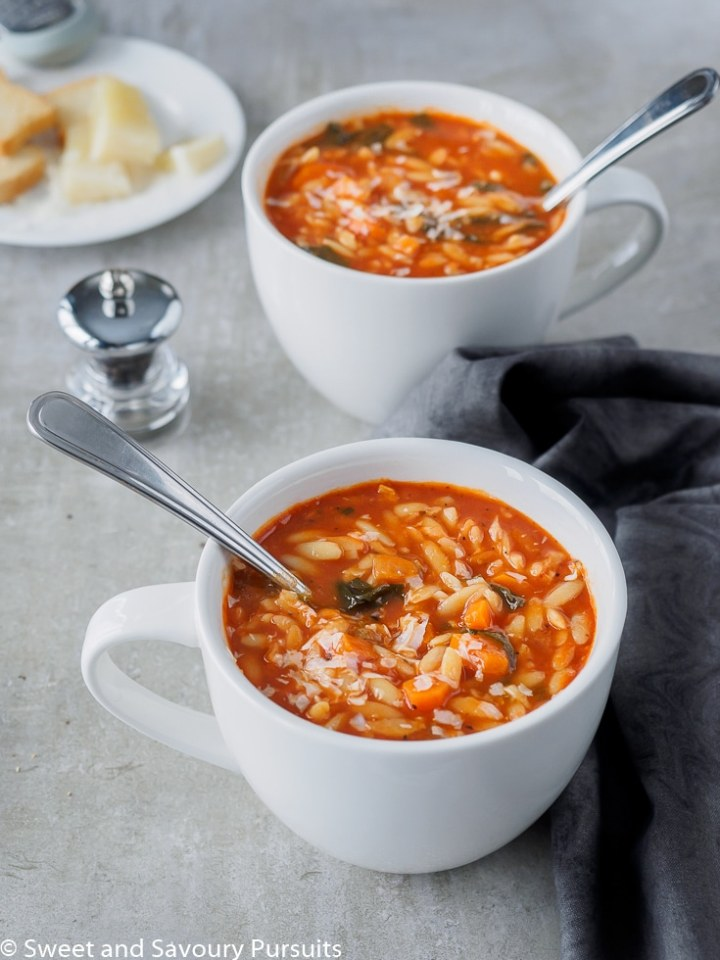 Tomato Orzo Soup served in large white mugs.