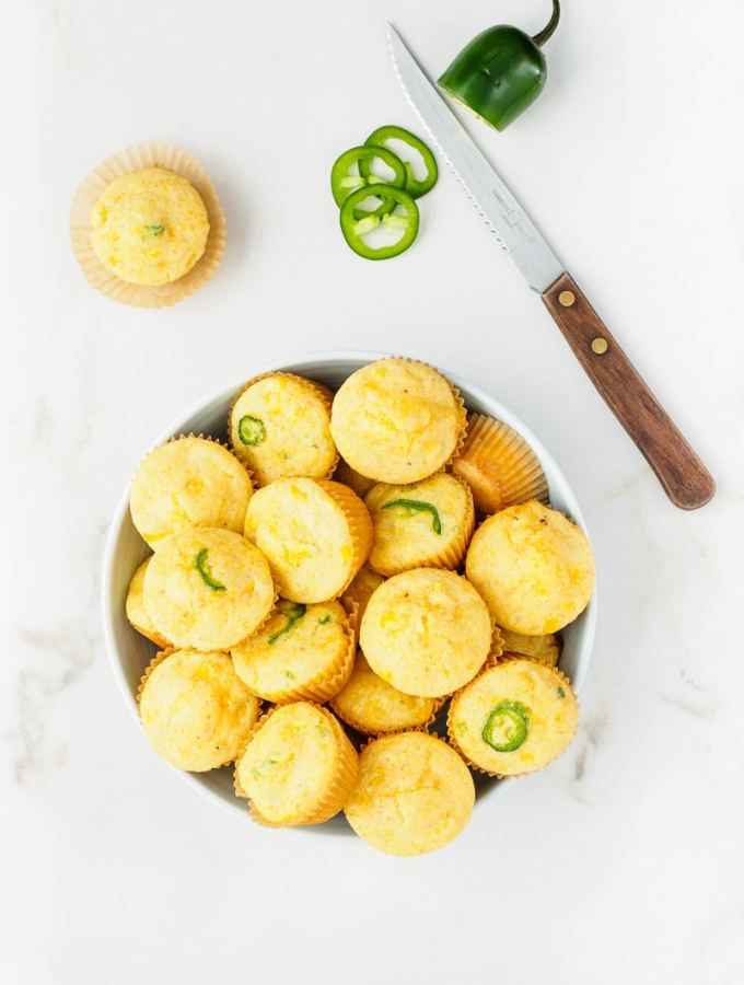Freshly baked Mini Cornbread Muffins with corn kernels and jalapeno in bowl.