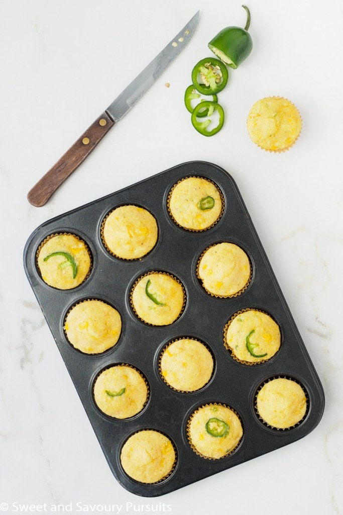Freshly baked Mini Cornbread Muffins still in the muffin tin with corn and jalapeno.