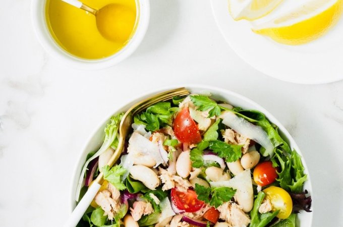 One bowl of White Bean and Tuna Salad served with a lemon and olive oil dressing on the side.