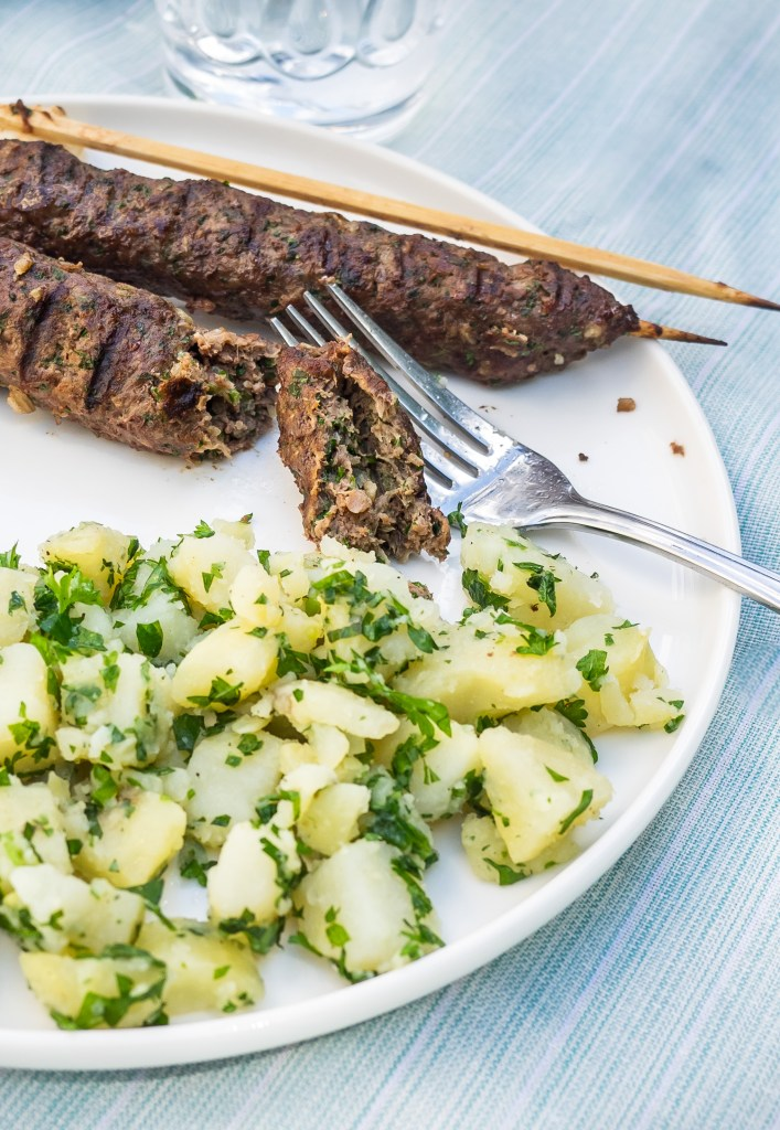 Plate of grilled beef kebabs served with potato salad.