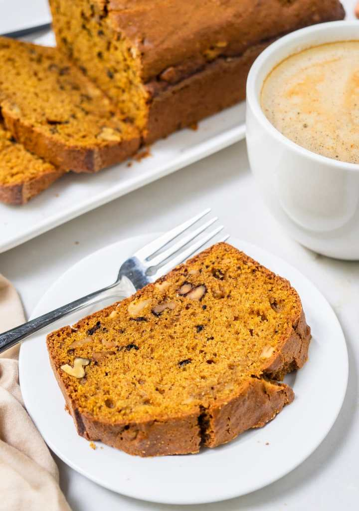 A slice of pumpkin bread on small white dish.