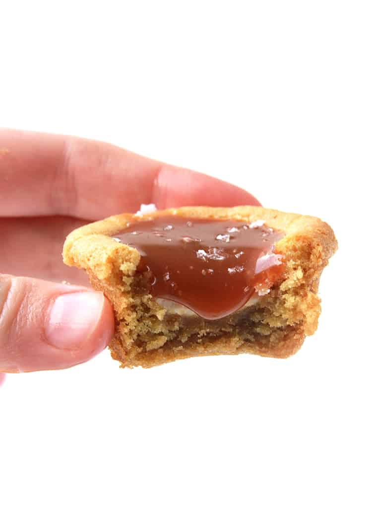 A hand holding a cookie cup filled with caramel sauce