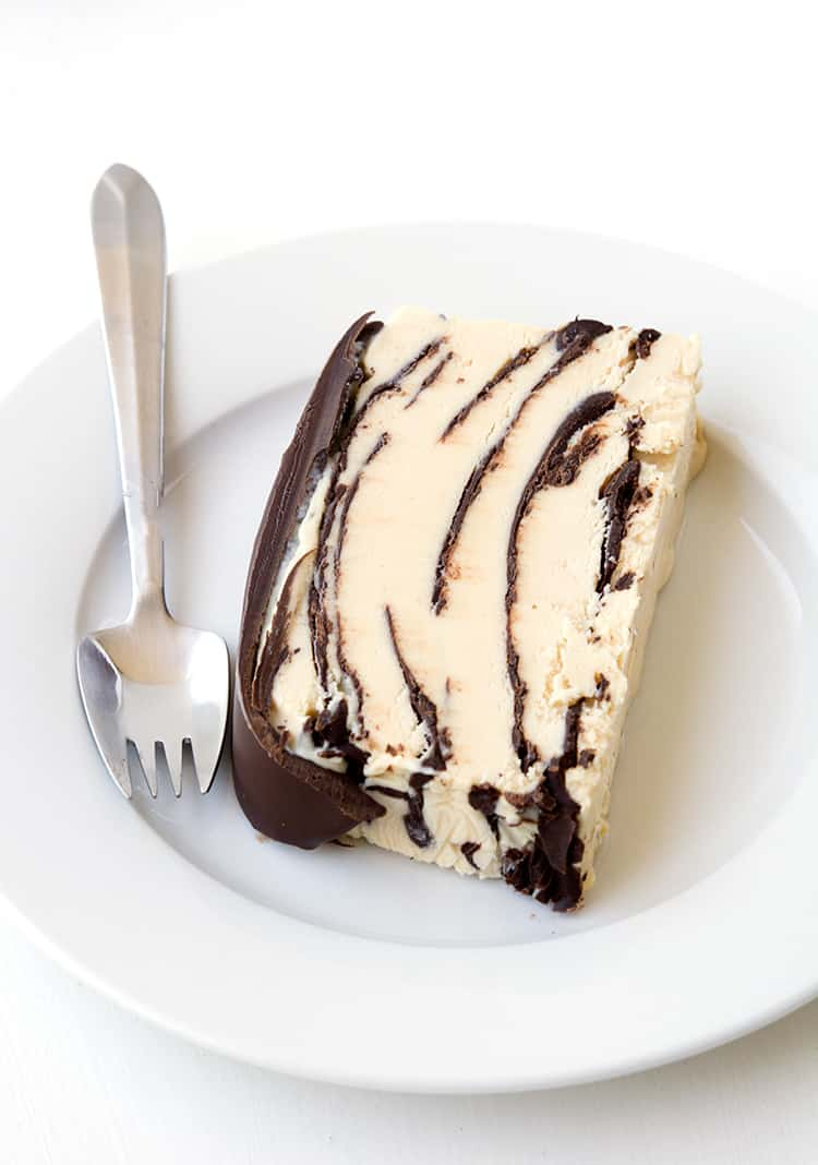 A slice of peanut butter ice cream cake on a white plate