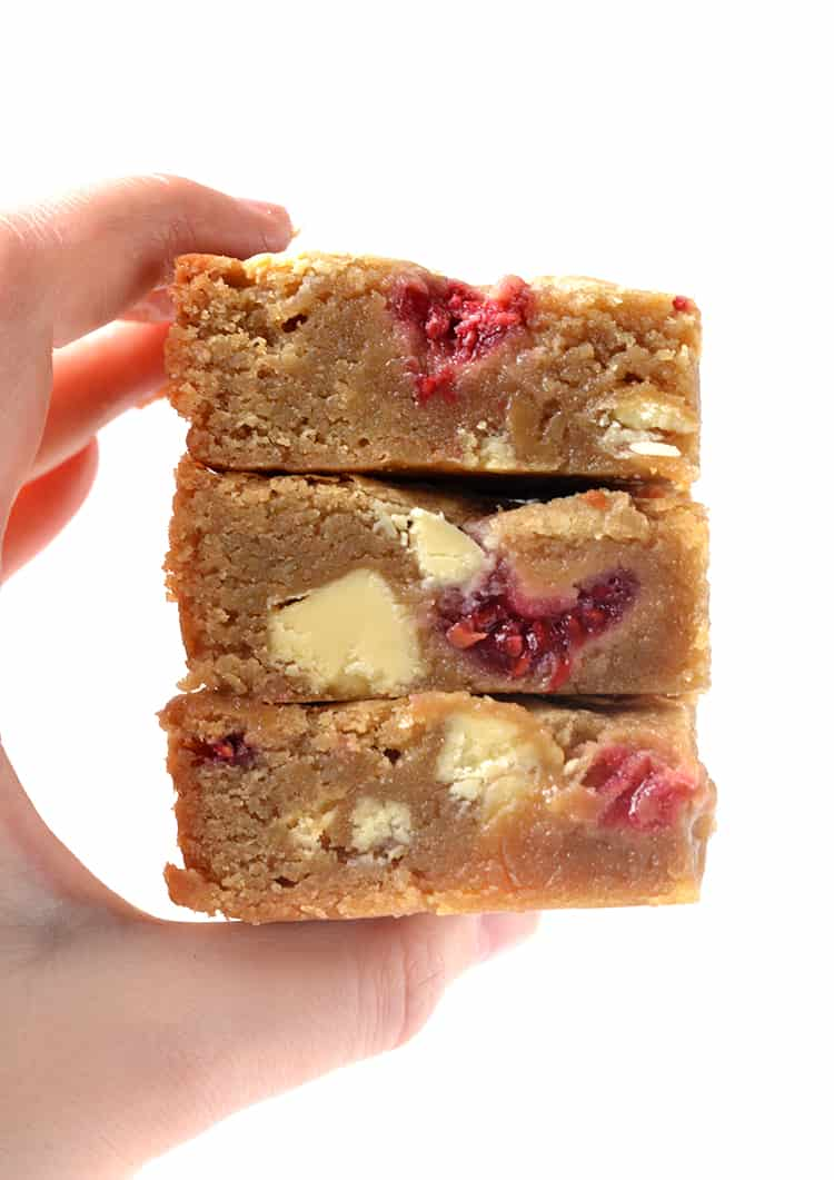 A hand holding a stack of White Chocolate and Raspberry Blondies