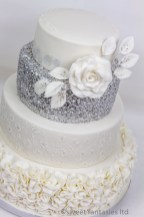 4 Tier white & silver wedding cake with petals & Rose