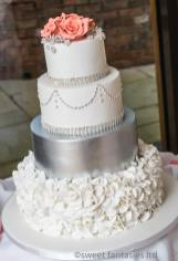 4 Tier round wedding cake withpetals on bottom tier, silver 2nd tier & roses on top tier