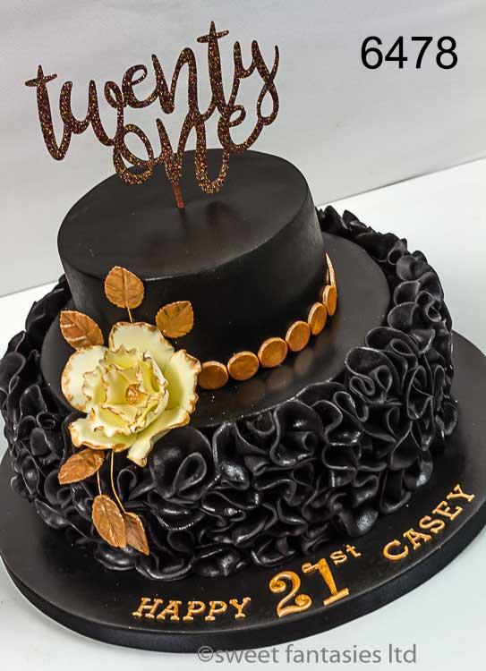 black 21st birthday cake with ruffles , flower & gold trim