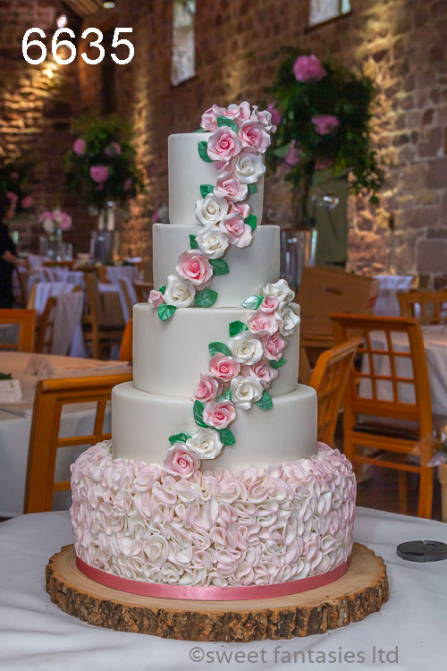 wedding cake with Pink ruffles & white tiers with pink & white roses