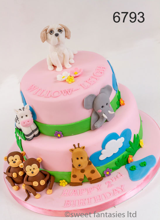 2 tier pink cake with jungle animals, & model dog on top