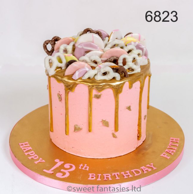 Pink cake with gold drip, biscuits & pretzels