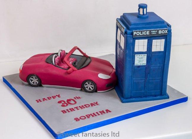 Sports car crashing into the tardis. birthday cake