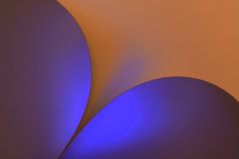 The light on the paper provides a contrast of complementary colors in abstract curves