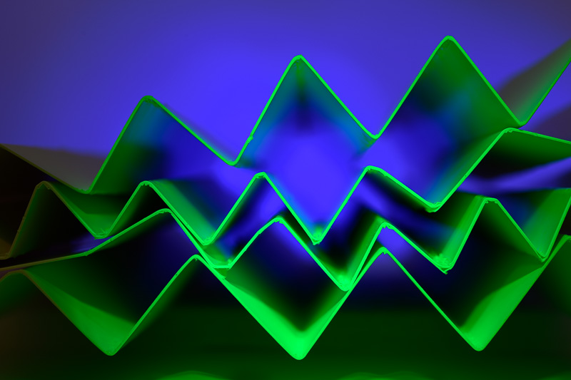 dramatic Image showing blue light on the background and green light on the front folded paper edge