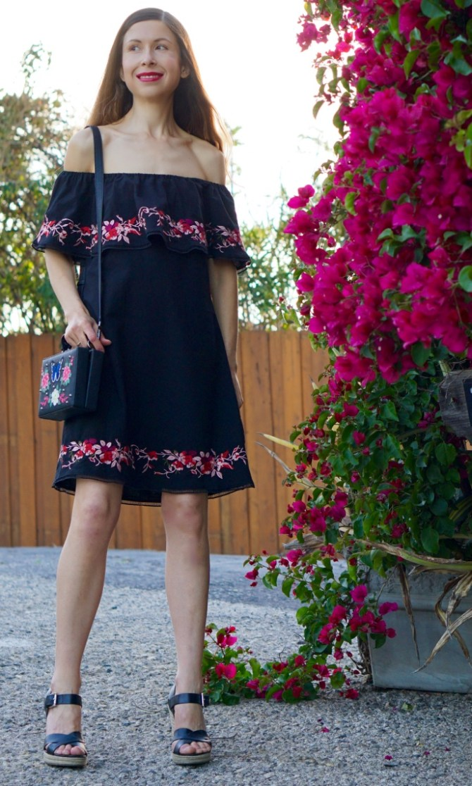 This embroidered black off-the-shoulder dress is pretty, trendy, colorful and super-versatile! It is simple and classy, yet it's fun and feminine! The Embroidered Mini Bag completes the look!