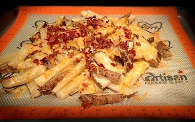 """Outback Steakhouse's Aussie Cheese Fries : 1 bag of Ore Ida """"Simply"""" Olive Oil-Sea Salt Country Style Fries 1 cup shredded Colby Jack cheese 5 slices bacon 2 green onions, chopped 1/2 cup to 1 cup good-quality Ranch or Honey Mustard dressing salt and pepper  Heat oven to 425. Spread fries onto baking sheet with a silicone mat on it. Bake according to package directions. Cook bacon until crispy in skillet and chop. When fries are crispy, remove from oven, season with salt and pepper. Pile fries into the center of the pan. Top with shredded cheese and bacon. Put back in oven for another 3-5 minutes to melt cheese. Remove and top with green onions. Serve with dressing on the side. """
