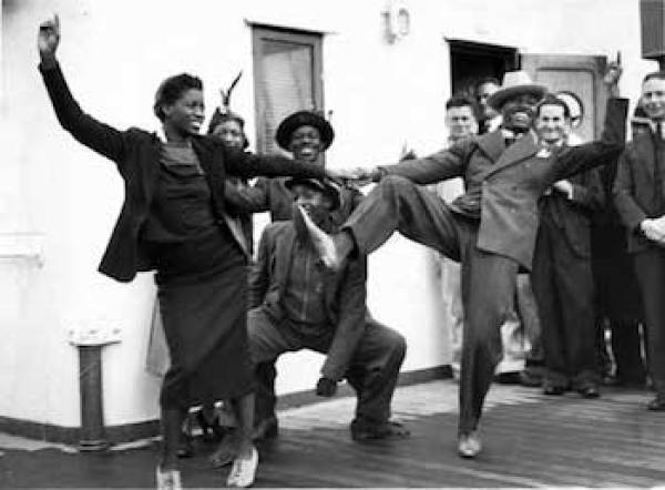 In 1903, The Charleston dance originated in the African American community on an island off the coast of Charleston, SC. The Charleston has its earliest origins in Central Africa as tribes in Africa perform similar movements in their dances. It did not receive widespread attention until the 1920s when it was adopted by the flappers, women who shortened their skirts and bobbed their hair. From its humble beginnings in South Carolina to the bright lights of Broadway, the Charleston swept the world up in a frenzy of frantic dancing.