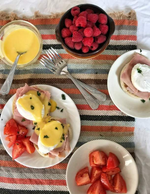 Overhead shot of Eggs Benedict with table set with tomatoes and raspberries