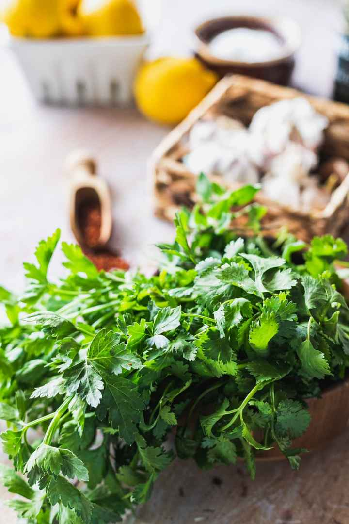 close up of the fresh oregano, parsley, and cilantro in a wooden bowl