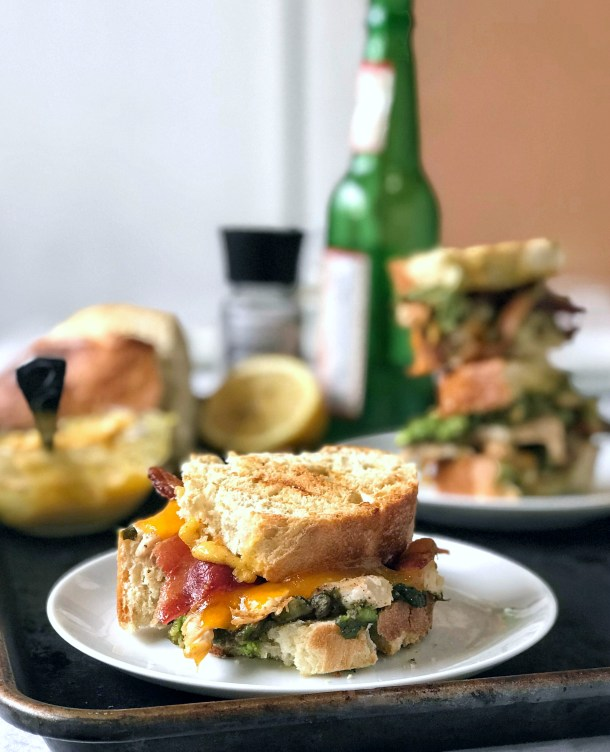 Chipotle Chicken Panini on a plate with sandwich stacks and aioli in the background on Sweet Tea and Thyme | www.sweetteaandthyme.com