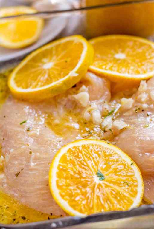 Chicken breast marinating in Cuban mojo criollo with galric and orange slices