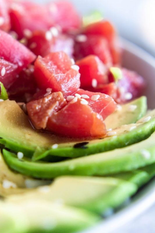 Close up of the marinated ahi tuna poke on slices of avocado, garnished with sesame seeds on Sweet Tea and Thyme | www.sweetteaandthyme.com