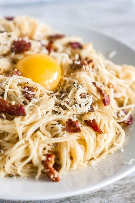 Close up of a glossy egg yolk on authentic spaghetti alla carbonara on Sweet Tea and Thyme | www.sweetteaandthyme.com