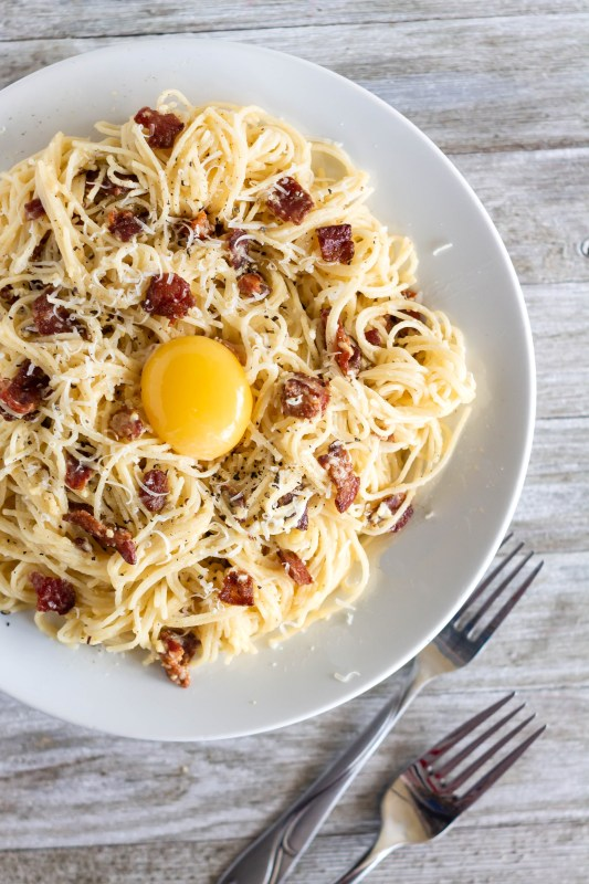 Overhead shot of a plate of authentic spaghetti alla carbonara with an egg yolk, garnished with bacon and parmesan on Sweet Tea and Thyme | www.sweetteaandthyme.com