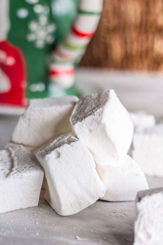 Foolproof Homemade Marshmallows piled on top of each other in front of a cup of hot chocolate on www.sweetteaandthyme.com