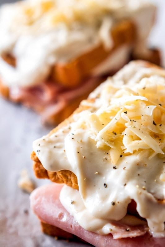 Close up of a croque monsieur sandwich before baking, with creamy mornay sauce and shredded gruyere cheese on top