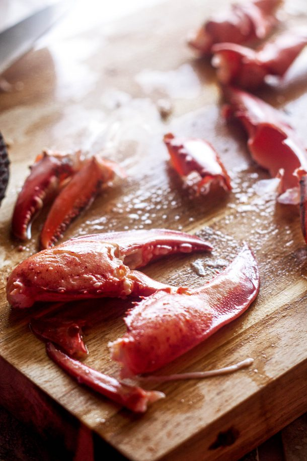 Lobster claw meat on a cutting board | Cooking a whole lobster is easier than you would think! This guide will teach you how to humanely kill a lobster, boil or steam them, shell them, and get every piece of meat from claw to tail.