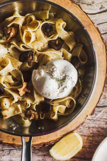 overhead shot of garlic mushroom pasta in a skillet with burrata cheese