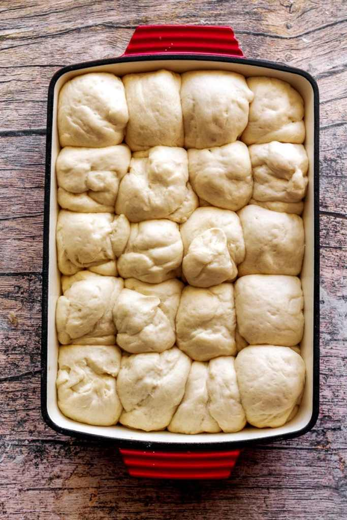overshot head of unbaked risen dinner rolls in pan