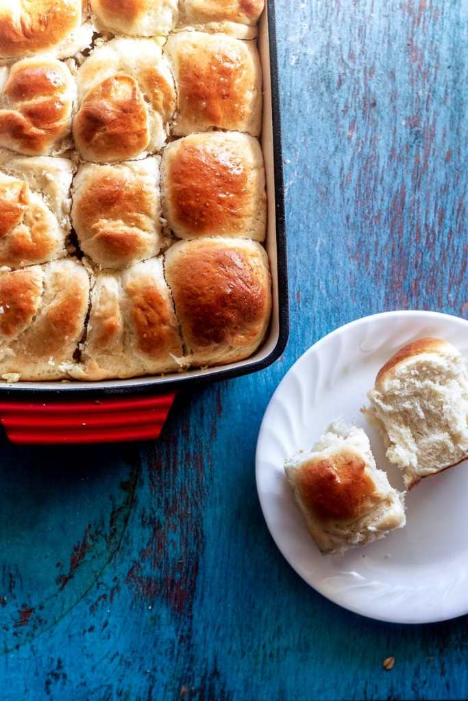 overhead shot of baked homemade dinner rolls on painted wood table