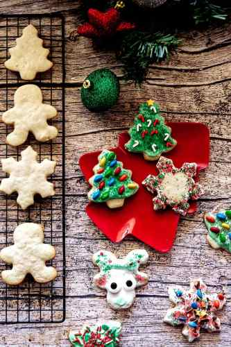 overhead shot of decorated and undecorated Christmas sugar cookies on a wooden table with garland and ornaments