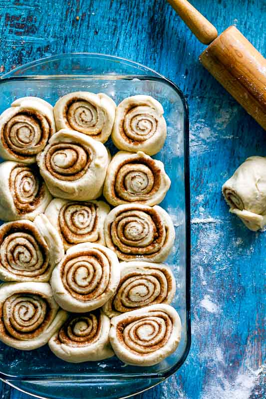 unbaked cinnabuns sitting in a glass baking dish with a rolling pin to the side on a blue wood surface