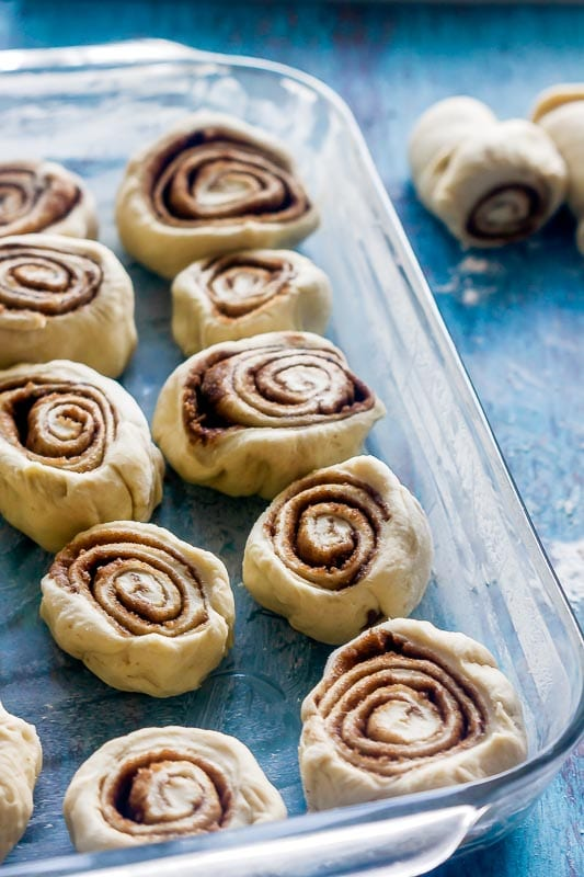 unrisen cinnamon rolls sit in a pyrex baking dish after being cut with floss