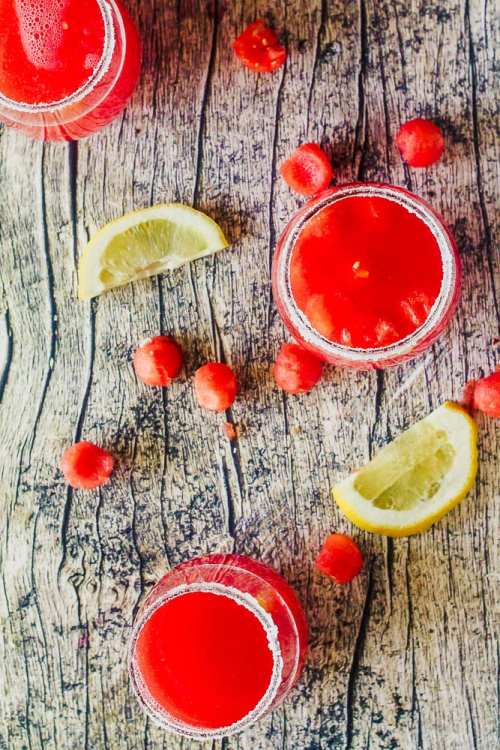 overhead shot of sugar-rimmed glasses filled with watermelon agua fresca on a wood table