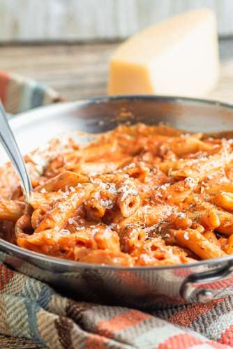 a pan of penne vodka sitting on a kitchen towel with parmesan cheese
