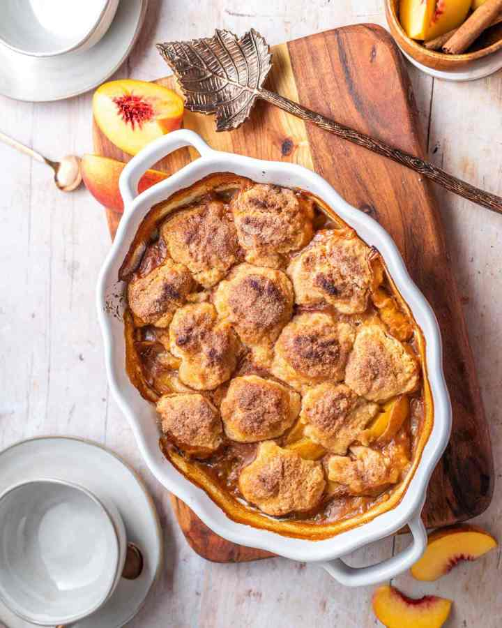 overhead of a baking dish full of bourbon peach cobbler with a cinnamon sugar biscuit topping and fresh peaches on a wooden tray