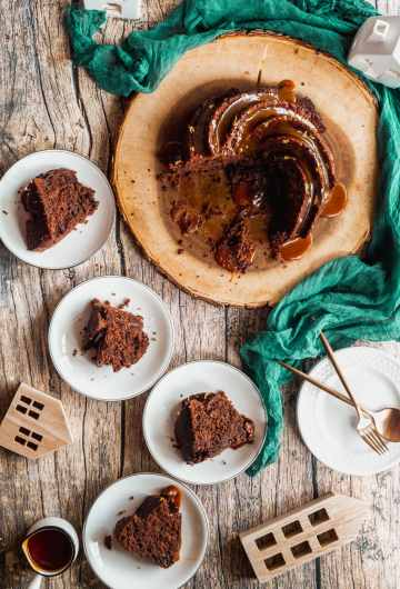 overhead shot of four slices of chocolate mayonnaise cake served on plates with the cake sitting on a wood platter