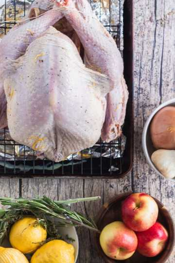 A dry brined turkey on baking sheet with aromatics surrounding it