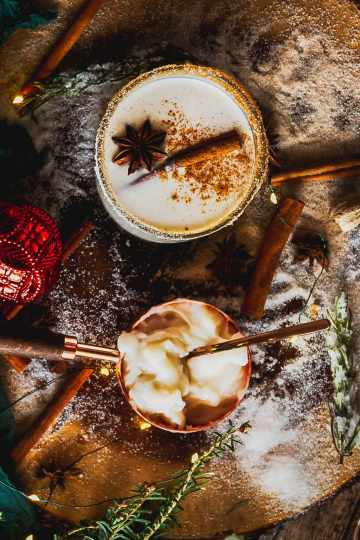 a cup of coquito sits with cinnamon sticks and a Christmas ornament along with a measuring cup full of Coco Lopez cream of coconut