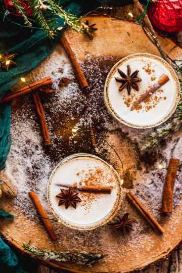overhead shot of two glasses of puerto rican coquito on a wood platter with cinnamon sticks, anise seed, and nutmeg, surrounded by holiday lights