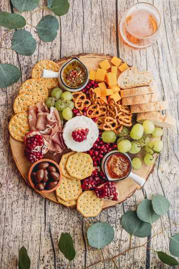 overhead meat and cheese board for two with goat cheese, cheddar, herbed oil, honey, crackers, and fresh fruit